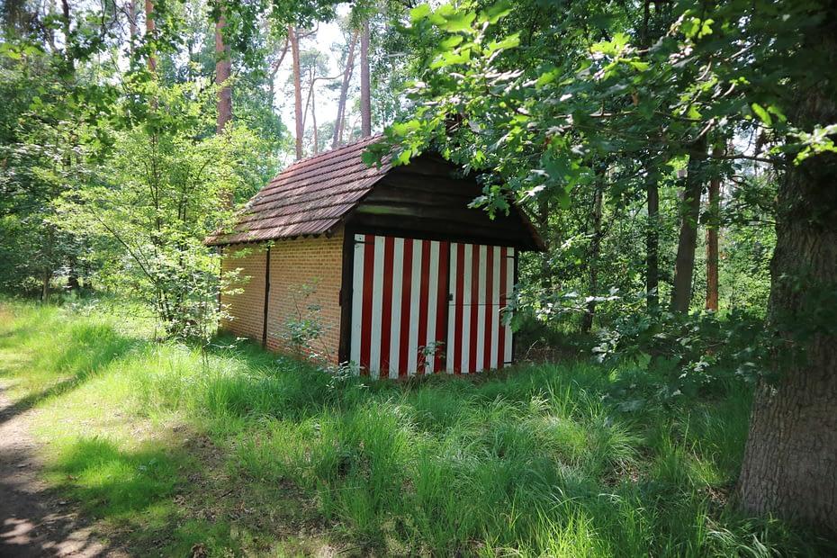 Een schuurtje in het natuurgebied 's Herenbos met poort in de typisch Kempische rood-wit kleuren.