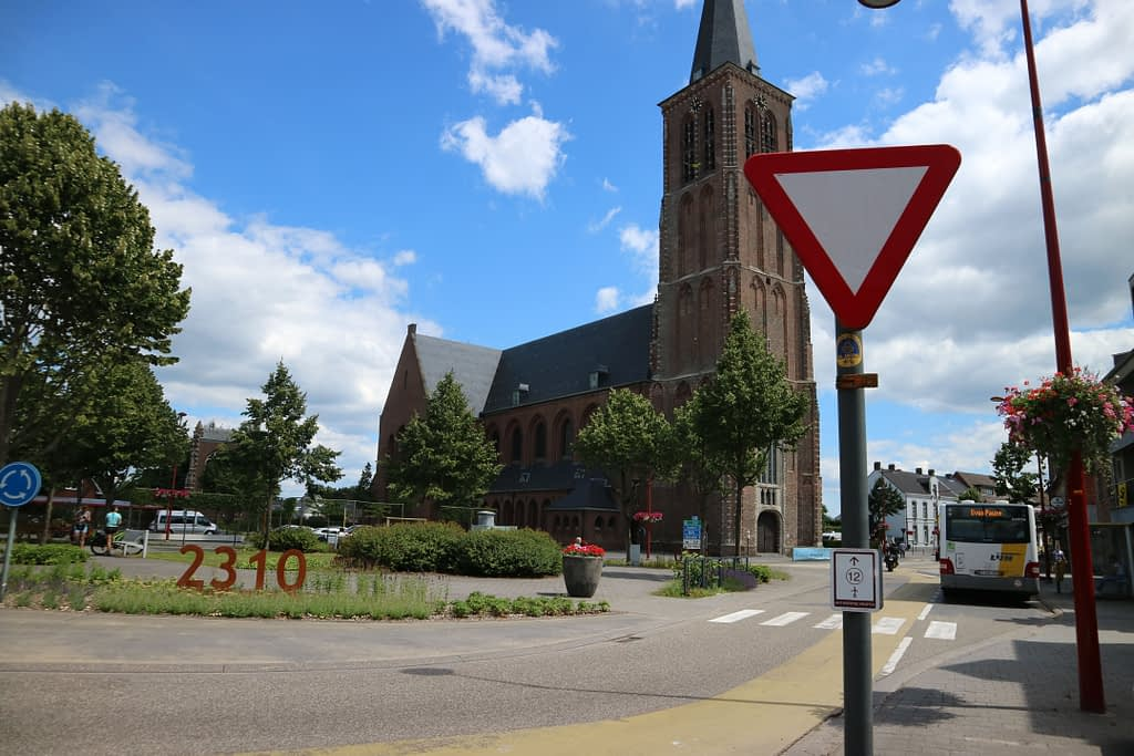 """Rotonde in het centrum van Rijkevorsel met zicht op de Sint-Willebrorduskerk en het """"oorspronkelijke' gevelfragment op de parking links van de kerk."""